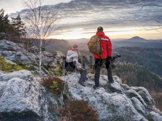 Nature photographers with big camera on tripod on summit