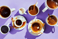 Flatlay of various cups with coffee and creamer on purple background