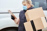 Paketbotin mit Mundschutz überprüft Lieferung mit Tablet