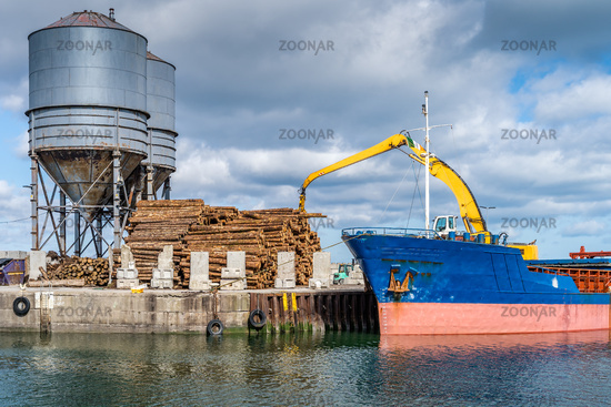 Crane with wood logs gripple loading timber on cargo ship