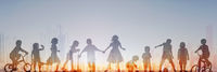 group of children playing with sunset sky and city skyline in background, people silhouette -