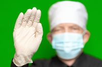 Doctor male in surgical face mask on defocus foreground put forward palm of hand in protective glove