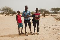Soungou Roungou, Senegal, Africa, January 19, 2020: horizontal photography of three boys, standing outdoors on a sunny day
