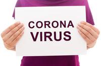 Girl holding white paper sheet with text Corona Virus