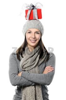 Glückliche Frau balanciert ein Geschenk auf Kopf