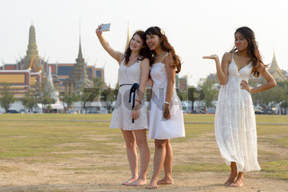 Three multi ethnic young beautiful women as friends together in the park