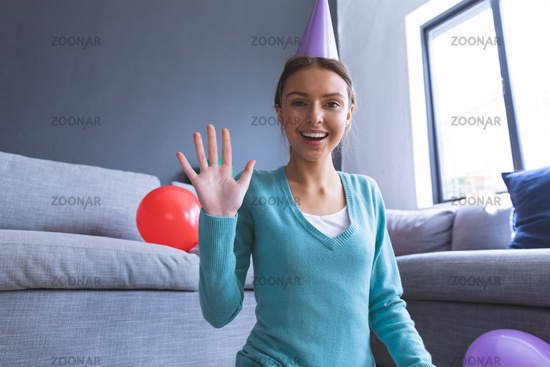 Portrait of woman in party hat smiling and waving  at home