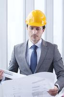 Architect in hardhat with blueprint