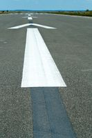 the markings of the runway, the white arrow painted on the pavement