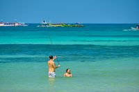 Boracay, Philippines - Jan 30, 2020: White beach of Boracay island. A guy and a girl take photos of themselves in the sea on a selfie stick.