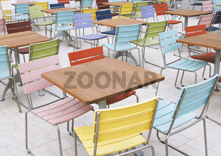 empty deserted street cafe or outdoor restaurant tables with multicolored chairs