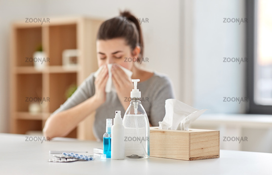 medicines and sick woman blowing nose to wipe