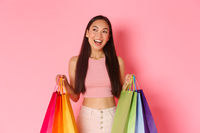 Beauty, fashion and lifestyle concept. Dreamy trendy asian girl buy everything for vacation, holding shopping bags and looking away with pleased smile, standing pink background.