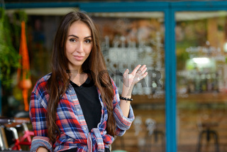 Young beautiful hipster woman at the coffee shop outdoors