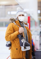 young man in mask with ice-skates on skating rink