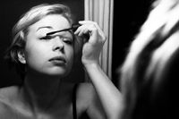 Woman getting ready for work doing morning makeup routine applying mascara in bathroom mirror at home. Beautiful caucasian girl applying eye make-up. Black and white image