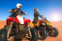 Quad driving people - happy smiling couple bikers in sand desert sunset.