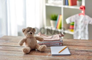 baby clothes, teddy bear toy and notebook