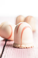 Sweet foam dessert. Marshmallow covered with strawberry icing.