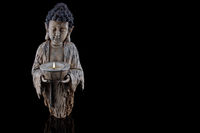 Buddha statue with burning candle isolated on black background with reflection