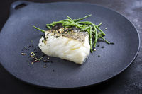 Gourmet fried Japanese skrei cod fish filet with glasswort and furikake as closeup on a modern design plate