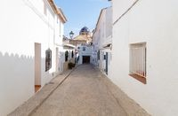 Narrow medieval street to the blue domed church in the old town center of Altea, Costa Blanca, Spain
