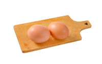 Two brown eggs on cutting board