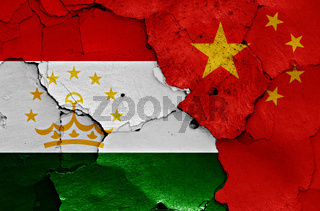 flags of Tajikistan and China painted on cracked wall
