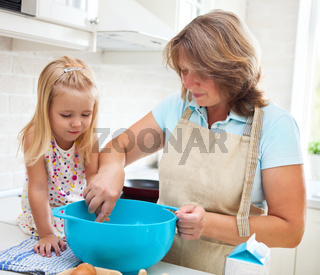 Little girl baking with her grandmother at home