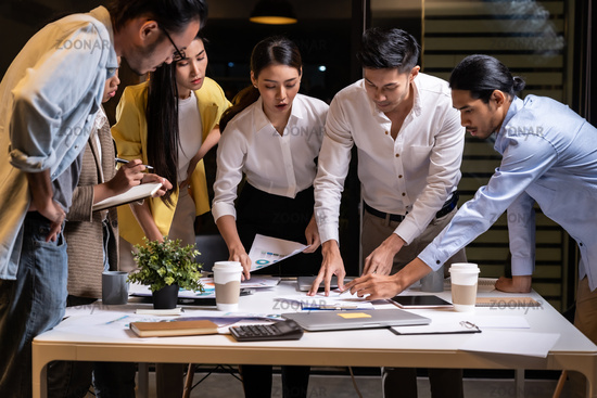 Working late, interracial asian business team brainstorm idea meeting.