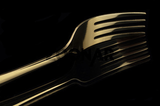 Gold fork on a black background with reflection. Cutlery.