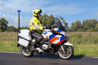 Motorcycle policeman riding in rural landscape near Urk, The Netherlands