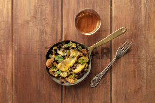 A photo of a rustic mushrooms and olives saute with mint, with a glass of white wine, shot from the top on a dark rustic background with a place for text