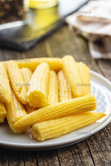 Pickled young baby corn cobs on plate