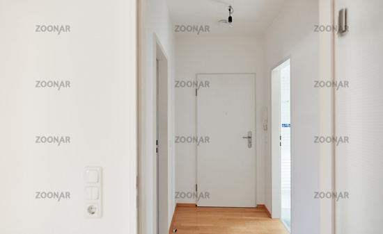 Flur mit Parkett und Wohnungstür in Wohnung nach Renovierung