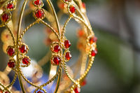 Closeup macro shot of beautiful golden Christmas decoration with red jewels and scenic bokeh
