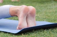 female legs on yoga mat close up
