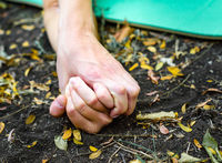 hands of people holding each other on the ground surrounded by leaves
