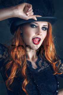 Beautiful woman portrait dressed as witch for Halloween party in witches hat with red hair and bright lips. Posing over dark magic forest background behind.