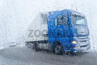 Lastwagen bei Regen und Schnee auf der Straße