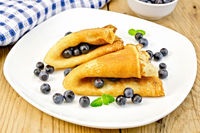 Pancakes with blueberries on wooden board
