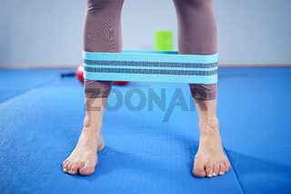 Athletic woman in sportswear barefoot using thick elastic fabric workout bands for stretch fitness booty loops, band for gym, weights squats, training muscles. Slim girl in good shape