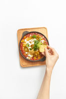 Woman's hand takes Shakshouka healthy food from the pan.