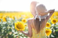Beautiful Woman With Hat in a Sunflower Field in summertime.
