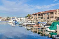 Boats docked at the harbour with waterfront homes in Huntington Beach California