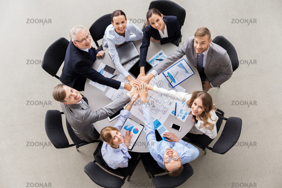 happy business people stacking hands