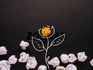 Concept for new ideas, yellow crumpled paper grows up as a flower