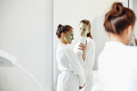 Charming women with facial masks in bathroom
