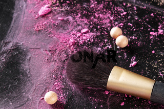 A make up brush with crushed cosmetics and pearls on a black background with copyspace