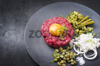 Gourmet tartar raw from beef fillet with yellow of the egg and gherkin with capers and onion rings as closeup on modern design plate with copy space